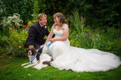 bride and groom sat on grass with dog Lincolnshire Wedding Photographer