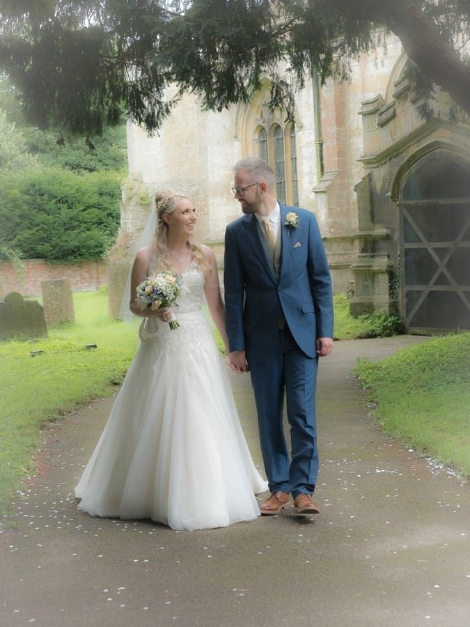 bride and groom walking down church path