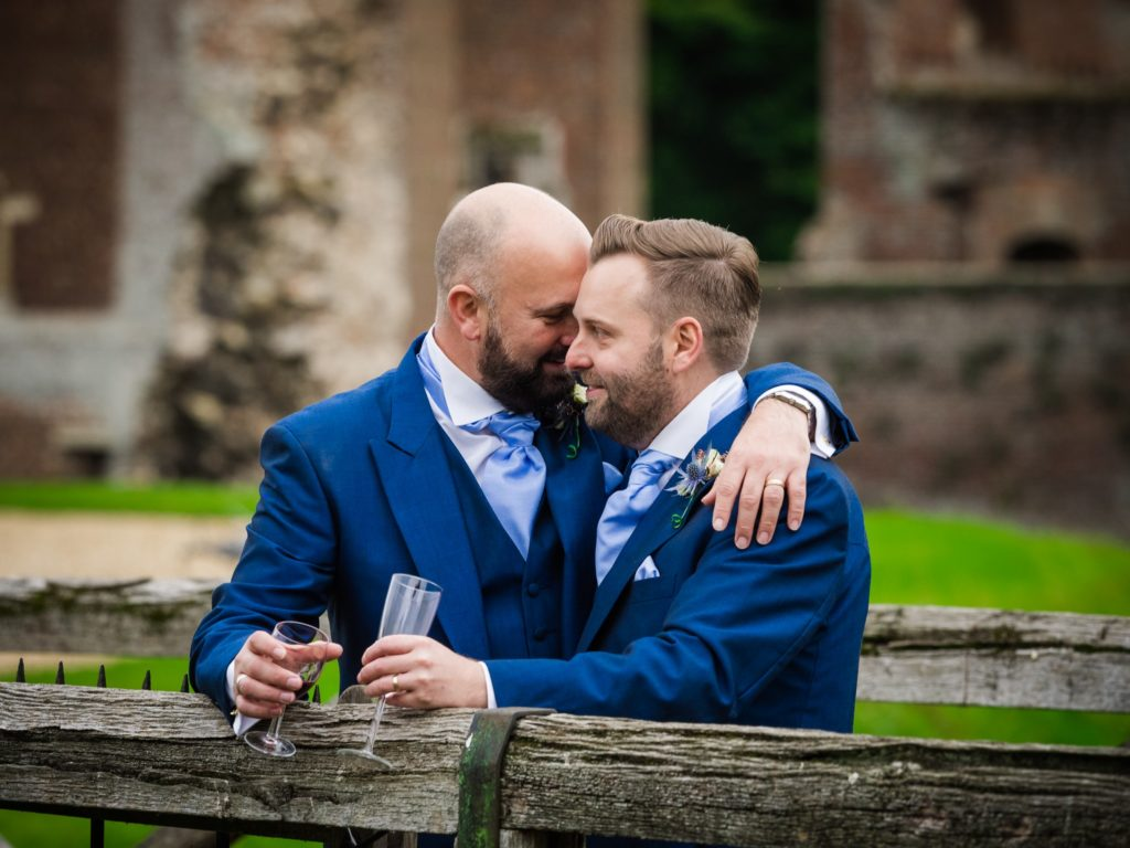 Gay grooms hugging