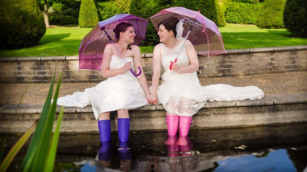 two brides sat by pond